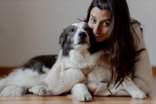 Femme soignante en laine pull étreignant drôle Border Collie chien tout en étant couché sur le sol en bois ensemble en regardant la caméra — Photo de stock