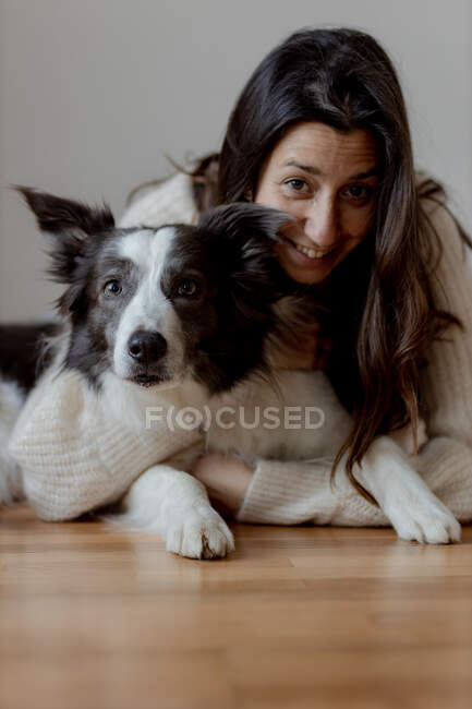 Caring female in woolen sweater hugging funny Border Collie dog while lying on wooden floor together looking at camera — Stock Photo