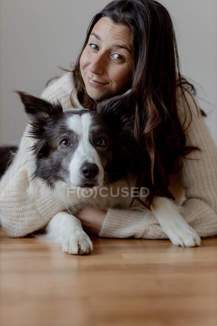 Fürsorgliche Hündin im Wollpullover umarmt lustigen Border Collie Hund, während sie gemeinsam auf dem Holzboden liegt und in die Kamera schaut — Stockfoto