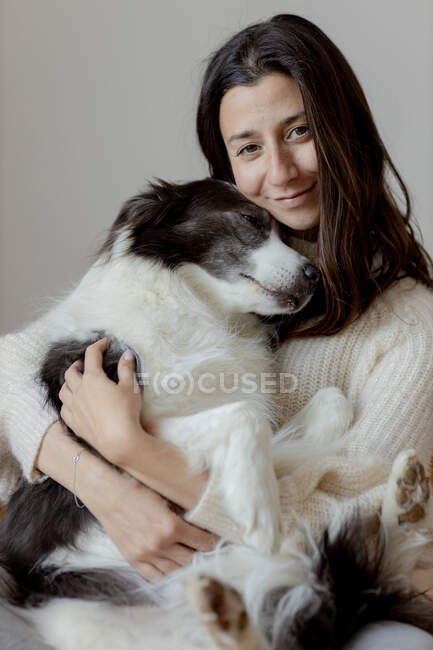 Fürsorgliche Hündin im Wollpullover umarmt lustigen Border Collie Hund, während sie gemeinsam auf dem Holzboden sitzt und in die Kamera schaut — Stockfoto