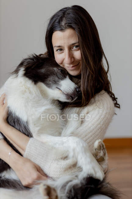 Caring female in woolen sweater hugging funny Border Collie dog while sitting on wooden floor together looking at camera — Stock Photo