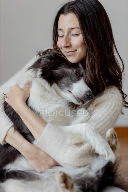 Fürsorgliche Hündin im Wollpullover umarmt lustigen Border Collie Hund, während sie gemeinsam auf Holzboden sitzt — Stockfoto