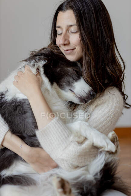 Caring female in woolen sweater hugging funny Border Collie dog while sitting on wooden floor together — Stock Photo