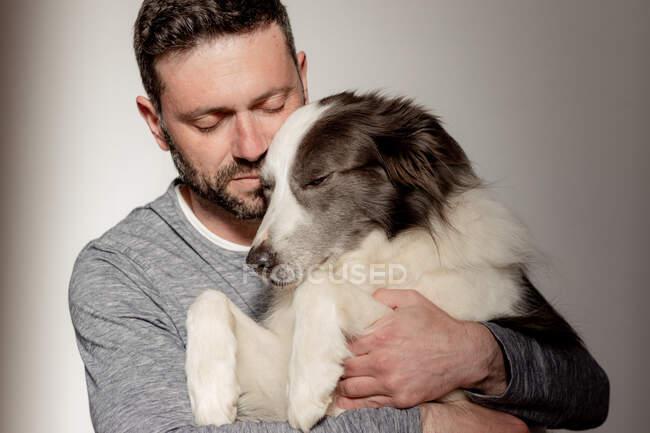 Мужчина в повседневной одежде обнимает и целует любимую собаку Пограничной Колли дома — стоковое фото