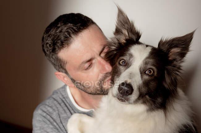 Homme en tenue décontractée donnant câlin et baiser à la frontière bien-aimée Collie chien à la maison — Photo de stock
