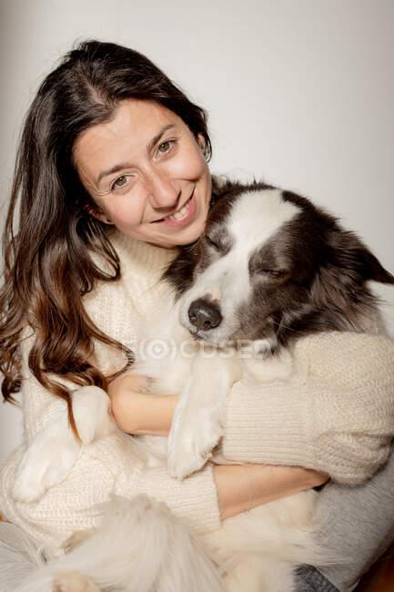 Cura femminile in maglione di lana abbracciare divertente Border Collie cane mentre seduti sul pavimento di legno insieme guardando la fotocamera — Foto stock