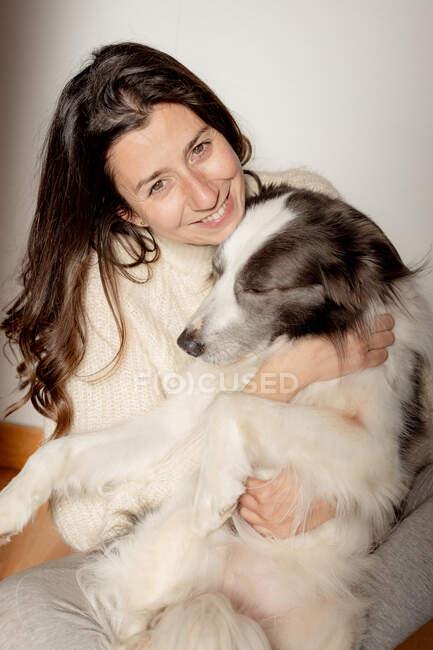 Carinhoso fêmea em blusa de lã abraçando engraçado Border Collie cão enquanto sentado no chão de madeira juntos olhando para a câmera — Fotografia de Stock