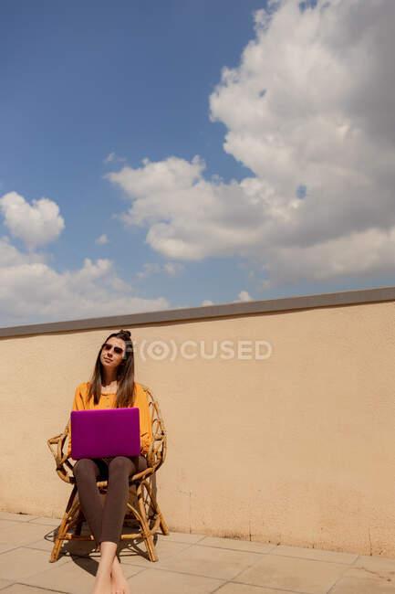 Брюнетка в повседневной одежде сидит на стуле и просматривает фиолетовый нетбук во время работы и наслаждается солнцем на террасе дома во время карантина — стоковое фото