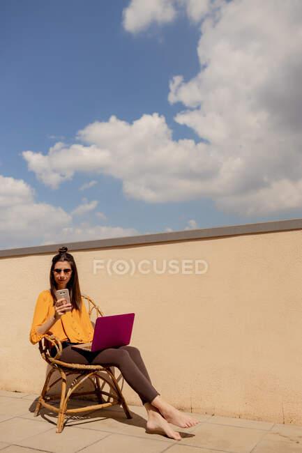 Позитивна жінка пише повідомлення на смартфоні і сидить з ноутбуком на кріслі на терасі, працюючи з дому в карантинний час. — стокове фото