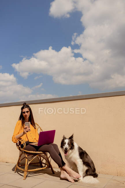 Brunette woman in casual outfit sitting on chair and browsing purple netbook while working and enjoying sunshine in terrace of house during quarantine — Stock Photo