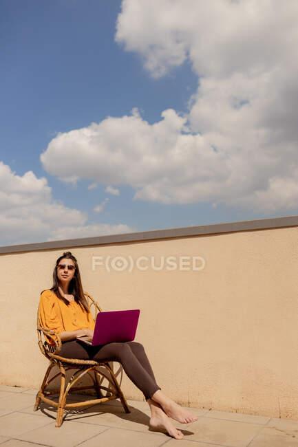 Жінка в повсякденному одязі сидить на стілець і переглядає фіолетовий ноутбук під час роботи і насолоджується сонцем на терасі будинку під час карантину. — стокове фото