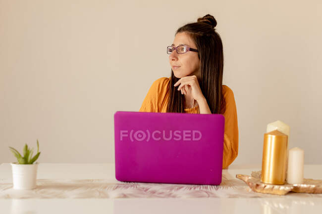 Young woman in casual outfit and eyeglasses smiling and looking at laptop while sitting at table at cozy room — Stock Photo