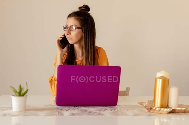 Ernste junge Frau in Brille und lässiger Kleidung arbeitet an rosa Laptop, während sie zu Hause in Quarantäne mit dem Smartphone spricht — Stockfoto