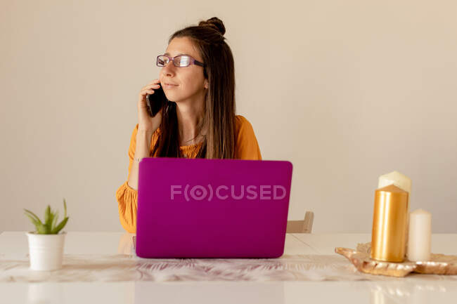 Serious young woman in glasses and casual clothes working on pink laptop while speaking on smartphone at home in quarantine time — Stock Photo