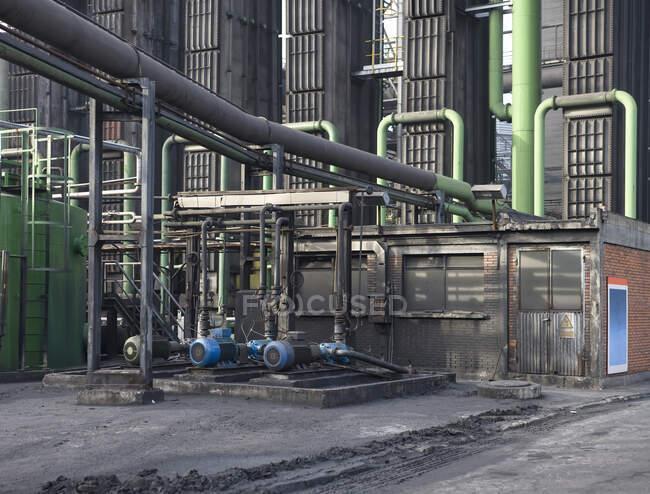 Baixo ângulo de fabricação de construção de fábrica com baterias de coque e mecanismos industriais metálicos com dutos — Fotografia de Stock