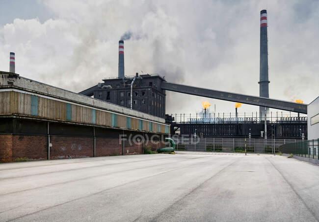 Edifícios industriais e tubos desgastados que emitem fumo e chamas na fábrica de coque — Fotografia de Stock