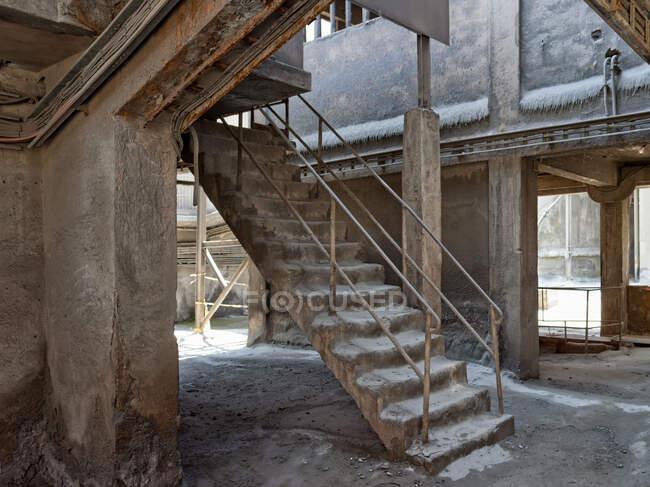 Escadaria de cimento resistente com grades enferrujadas que levam à entrada traseira da oficina envelhecida no território da fábrica abandonada na manhã fria de inverno — Fotografia de Stock