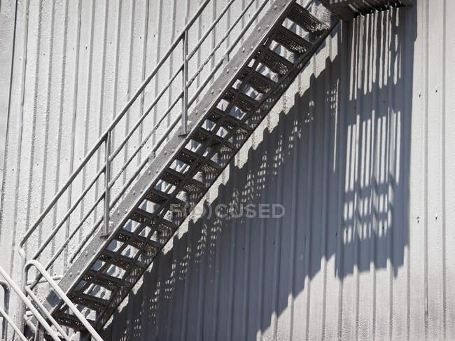 Escadas empoeiradas com corrimão colocado na parede de construção de metal no dia ensolarado dando longa sombra na parede de tecido — Fotografia de Stock