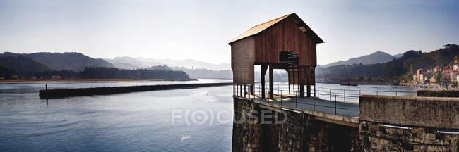 Gazebo in legno sul molo vicino alla tranquilla acqua di mare a Porto di San Esteban de Pravia, Spagna — Foto stock