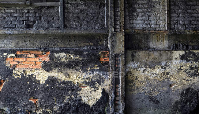 Grungy brick wall with crumbling dirty plaster located inside aged abandoned industrial facility — Stock Photo