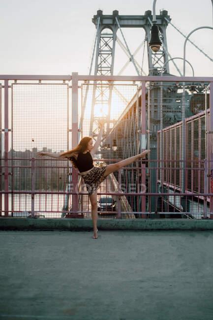 Seitenansicht einer anmutigen Tänzerin im Rock, die mit ausgestreckten Armen auf Zehenspitzen balanciert, während sie choreografische Elemente vor dem Hintergrund der Stadtlandschaft übt — Stockfoto
