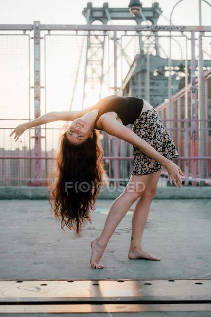 Seitenansicht der jungen anmutigen Tänzerin in lässigem Rock, die in Rückenbeuge auftritt, während sie barfuß auf der Brücke im Gegenlicht steht — Stockfoto