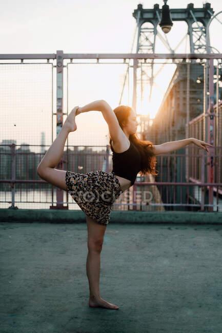 Seitenansicht einer flexiblen Frau in Freizeitkleidung, die Yoga in Tanzpose praktiziert, während sie barfuß im Gegenlicht vor dem Hintergrund der Stadtlandschaft steht und wegschaut — Stockfoto