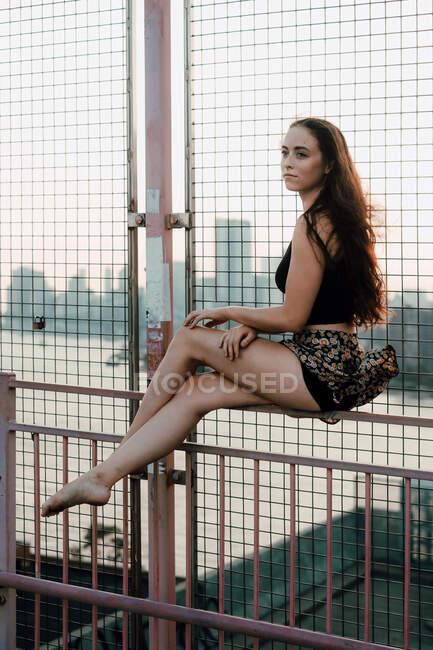 Vista laterale della donna graziosa in equilibrio sulla recinzione metallica del ponte urbano mentre seduto a piedi nudi sullo sfondo del paesaggio urbano e guardando altrove — Foto stock