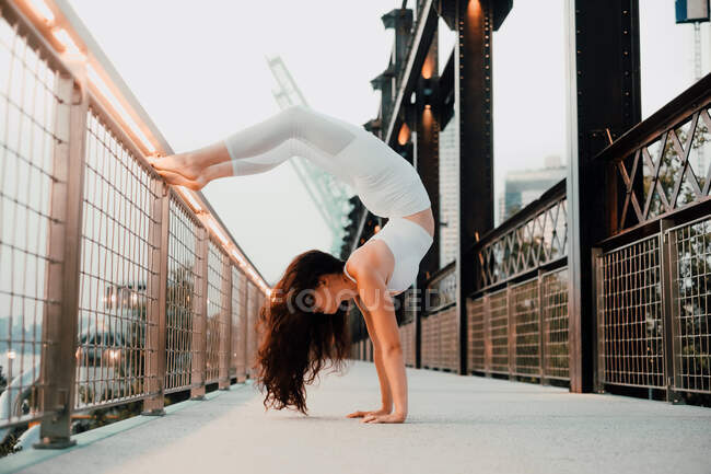 Low angle side view of flexible woman in sports bra and leggings performing scorpion handstand while exercising barefoot and leaning on metal railing in city — Stock Photo
