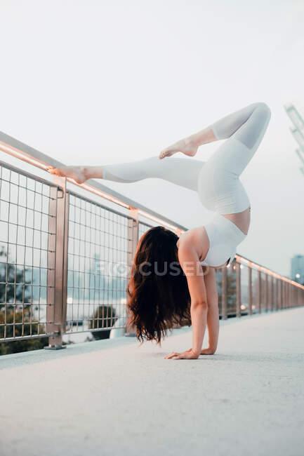 Vue latérale à angle bas de la femme flexible dans le soutien-gorge de sport et leggings effectuant le support à main scorpion tout en faisant de l'exercice pieds nus et en s'appuyant sur une rampe en métal en ville — Photo de stock