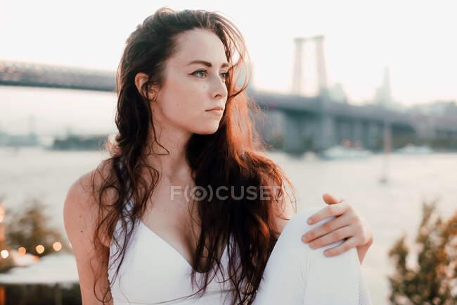 Wunderschöne Frau mit langen Haaren, die helle Kleidung trägt und auf dem Hintergrund von Brücke und Fluss sitzt, während sie entspannt wegschaut — Stockfoto
