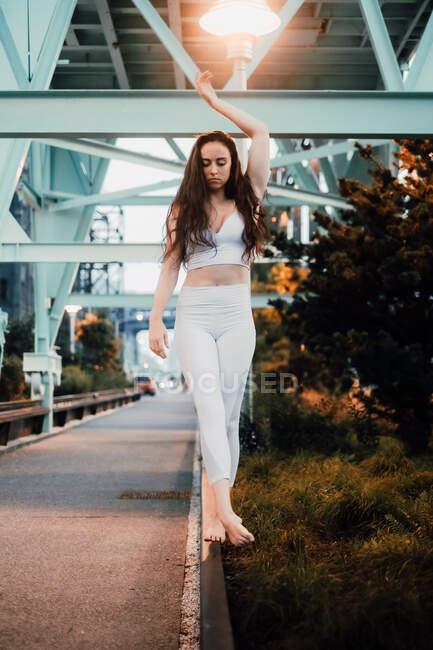 Юная стройная женщина в спортивном топе и леггинсах, стоящая босиком на тротуаре и изящно поднимающая руку в вечернем городе — стоковое фото