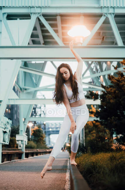 Young slim woman in sports top and leggings standing barefoot on pavement curb and raising arm gracefully in evening city — Stock Photo