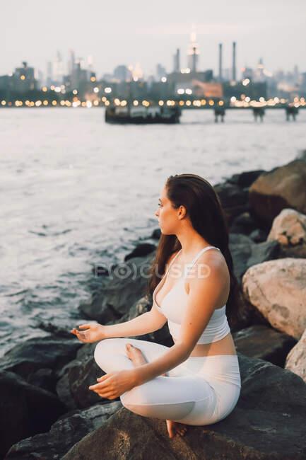 З іншого боку зору концентрована жінка в активаціях сидить на камені на набережній, практикуючи йогу. — стокове фото