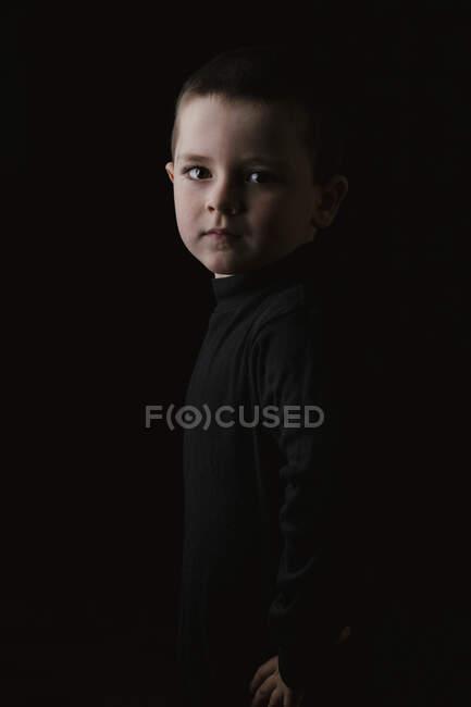 Маленький ребенок в черной водолазке смотрит в камеру, позируя руками на бедрах в темной студии. — стоковое фото