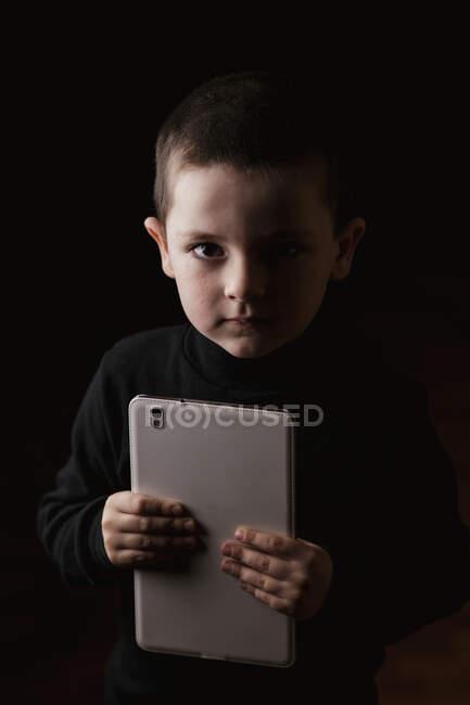 Очаровательный серьезный ребенок в повседневной одежде держит планшет в руках и смотрит на камеру с решительным взглядом изолированы на черном фоне — стоковое фото