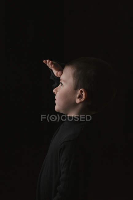 Portrait de petit garçon réfléchi pendant la prise de vue en studio sur fond noir — Photo de stock