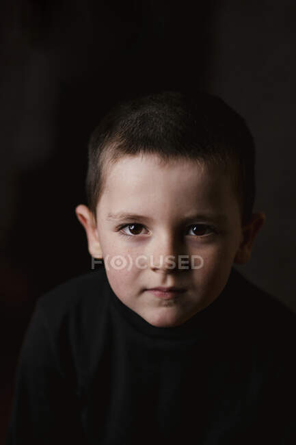 Portrait of thoughtful little boy looking at camera during taking studio shot against black background — Stock Photo
