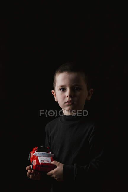 Portrait d'un petit garçon réfléchi tenant dans les mains la voiture rouge et regardant la caméra pendant la prise de vue en studio sur fond noir — Photo de stock