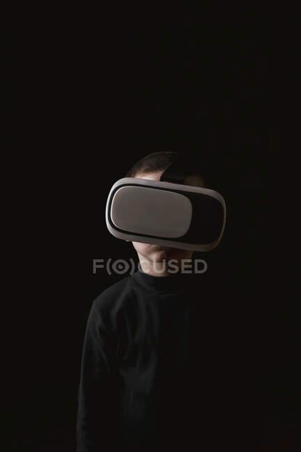 Ребенок в черном свитере и с VR-гарнитурой, стоящий у черной стены — стоковое фото
