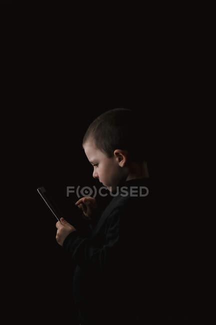 Criança séria adorável em desgaste casual segurando tablet em mãos com determinado olhar isolado no fundo preto — Fotografia de Stock