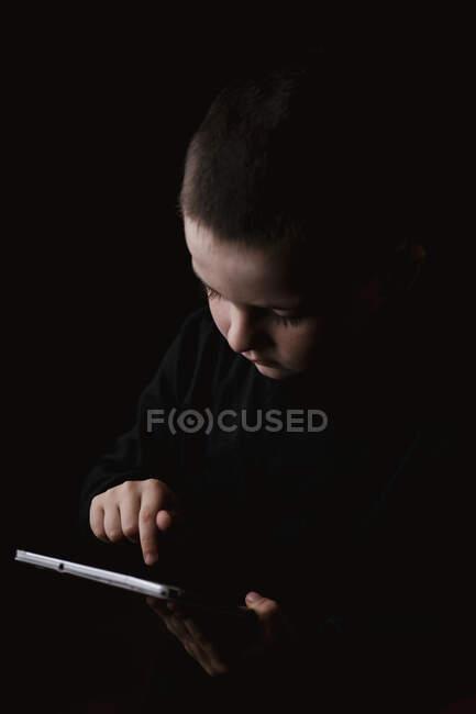 Очаровательный серьезный ребенок в повседневной ношении планшета в руках с решительным взглядом изолированы на черном фоне — стоковое фото