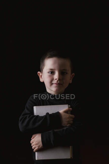 Adorable serious child in casual wear holding tablet in hands and looking at camera with determined look isolated on black background — Stock Photo