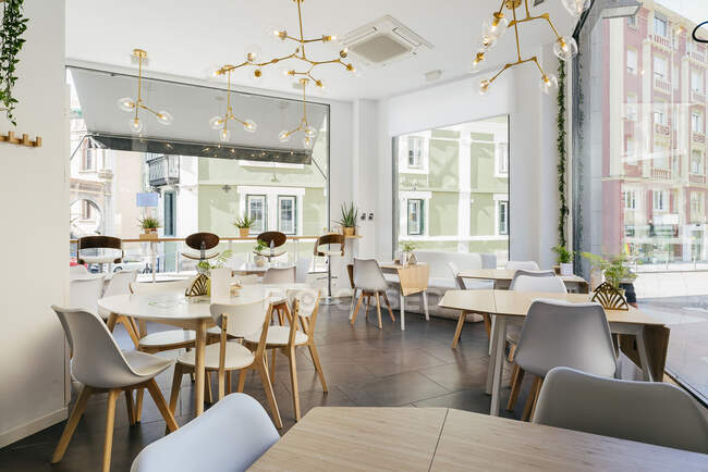 Interior of spacious light contemporary restaurant with big windows decorated with exotic plants and cozy chairs at tables under creative pendant lamps — Stock Photo