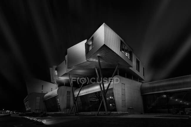 Angle bas de l'extérieur noir et blanc du bâtiment futuriste contemporain situé sur la rue de la ville en soirée — Photo de stock