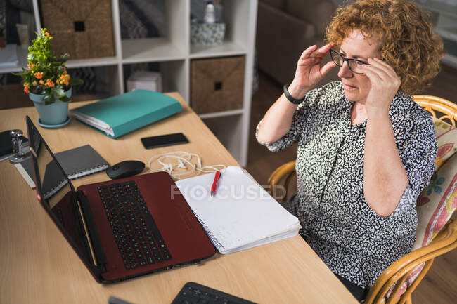 Side view of focused adult woman in casual clothes enjoying music in earphones with closed eyes while resting during work on laptop and notebook — Stock Photo