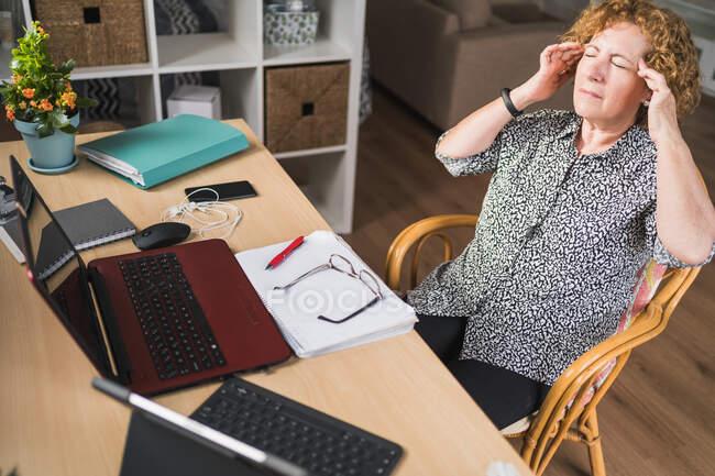 Desde arriba vista de adulto concentrado freelancer femenina frotando las sienes mientras descansa en la silla con los ojos cerrados durante el trabajo con documentos y gadgets - foto de stock