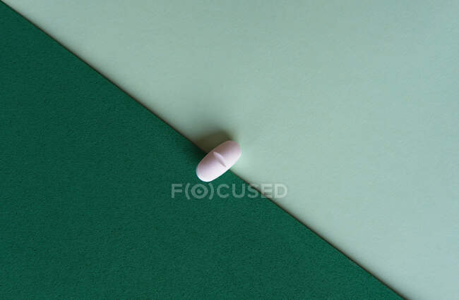 Top view of prescription pill for flu treatment placed on green and turquoise sheets of paper — Stock Photo
