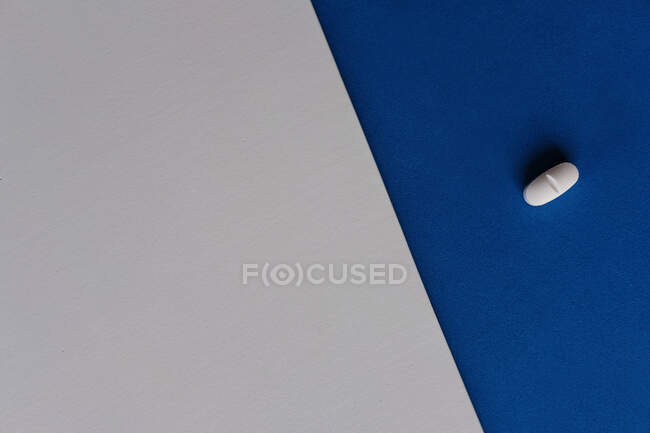 Top view of prescription pill for flu treatment placed on gray and blue sheets of paper — Stock Photo