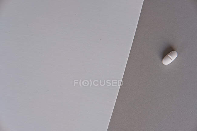 Top view of prescription pill for flu treatment placed on gradient gray sheets of paper — Stock Photo